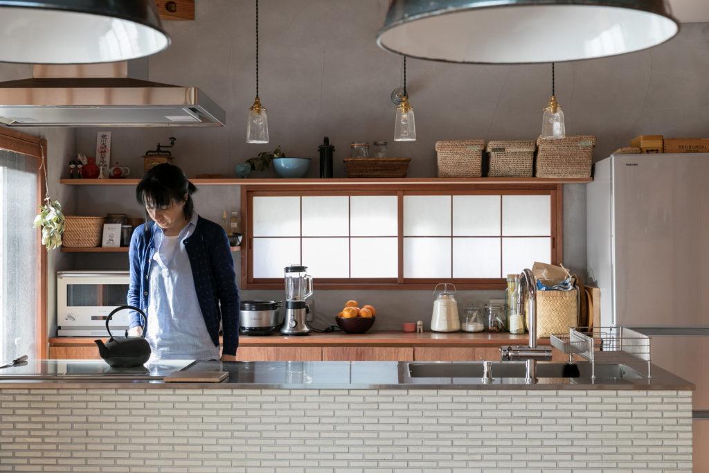 タイル張りのキッチン。天板はステンレス。「プロパンガスを使う地域なので、コンロはIHにしました」