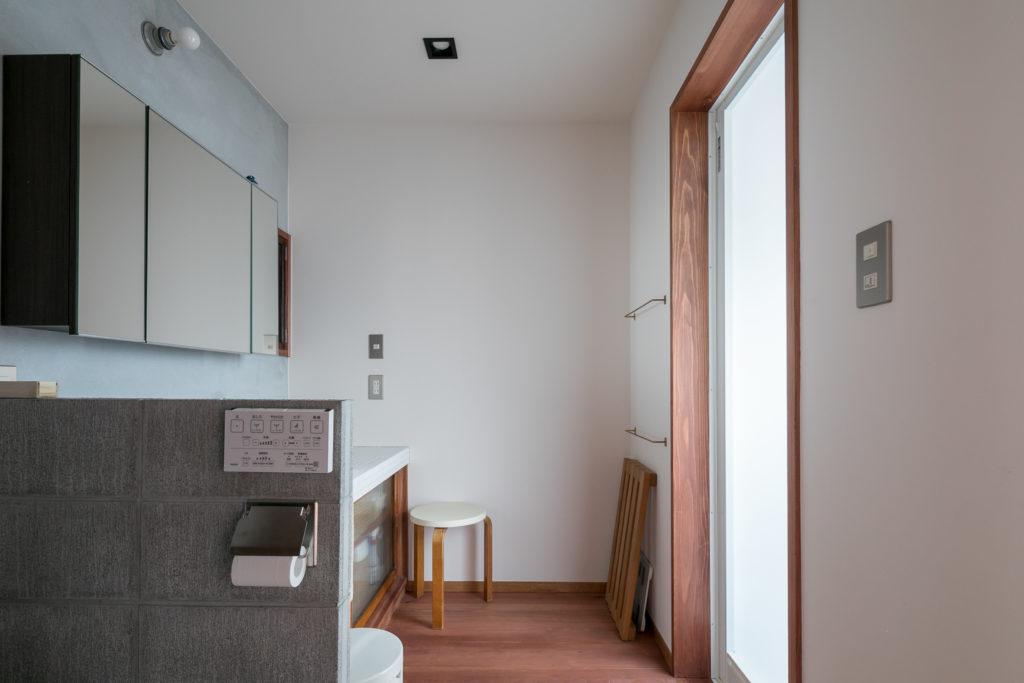 トイレと洗面台の間はコンクリートブロックで仕切った。洗面台の下の扉はガラスの引き戸にしている。