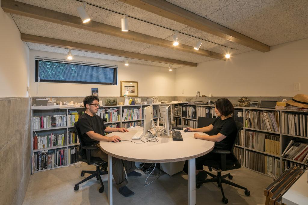 半地下の仕事スペースは、壁に向かって仕事はしたくないと、中央に円形のテーブルを置いた。