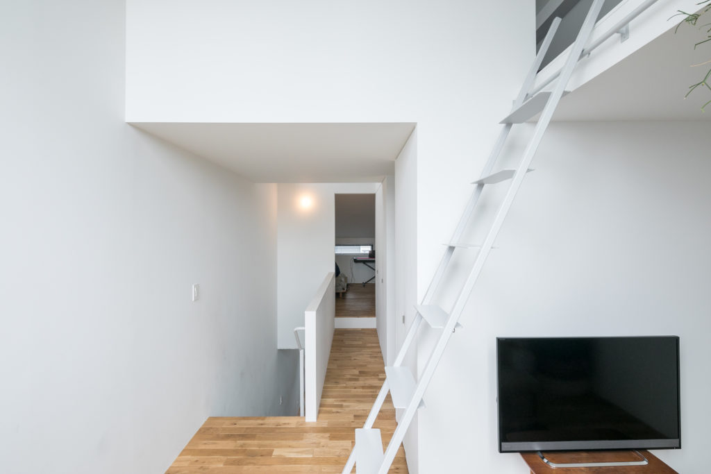 ダイニングから上がったフロアにはテレビを観たりする小さなリビングスペースを。奥が子供部屋で、梯子の上のロフトは夫婦の寝室。