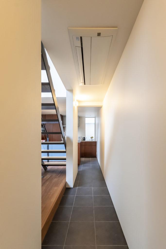 浴室側からキッチンを見る。キッチンの開口はエントランス部分の吹き抜けに面している。