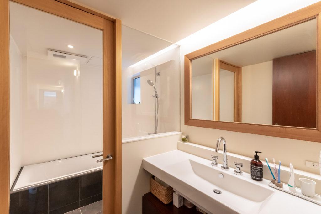 Hさんの希望で浴室の扉と壁をガラスにした。扉と鏡のフレームを木にしたのは奥さんのリクエストだった。