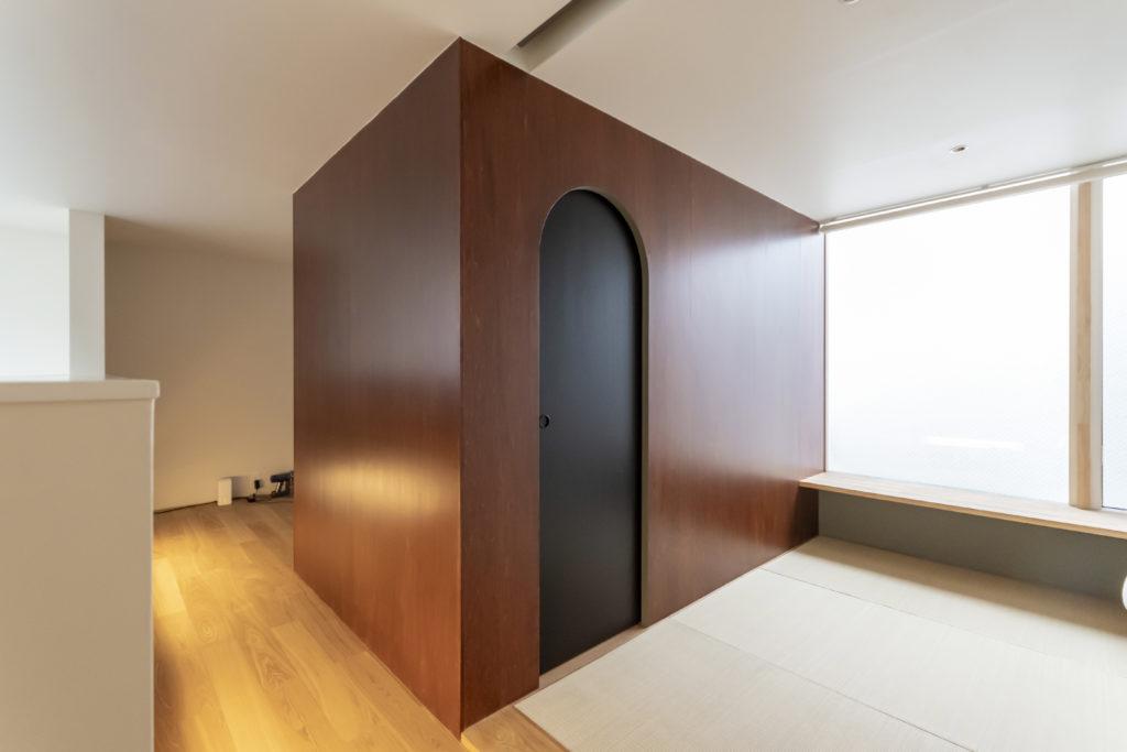 ウォークインクローゼットの扉上部のアールのラインが空間の雰囲気を和らげている。奥は将来の子ども部屋。
