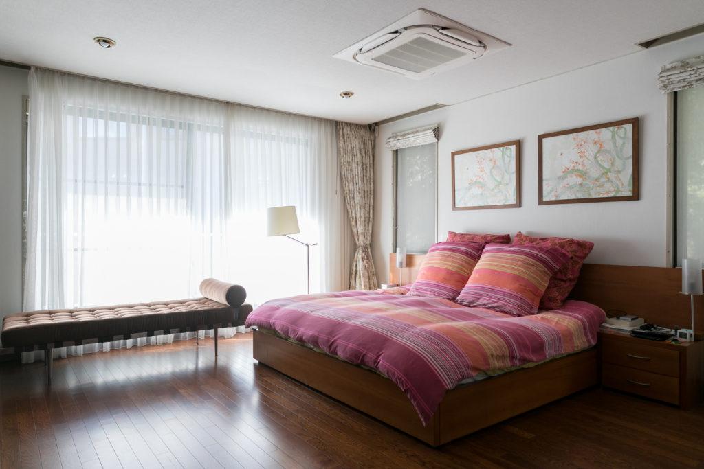 光がたっぷりと入る寝室。私物のベッドは、コロンビアから持ってくるのに苦労したそう。飾られている絵はコロンビアのロレンザ・パネロというアーティストの作品。