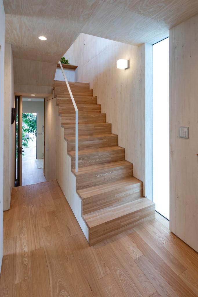 玄関から見る。階段の段差は低めに設定。数段降りた奥がサニタリールーム、その奥が勝手口へと続く。