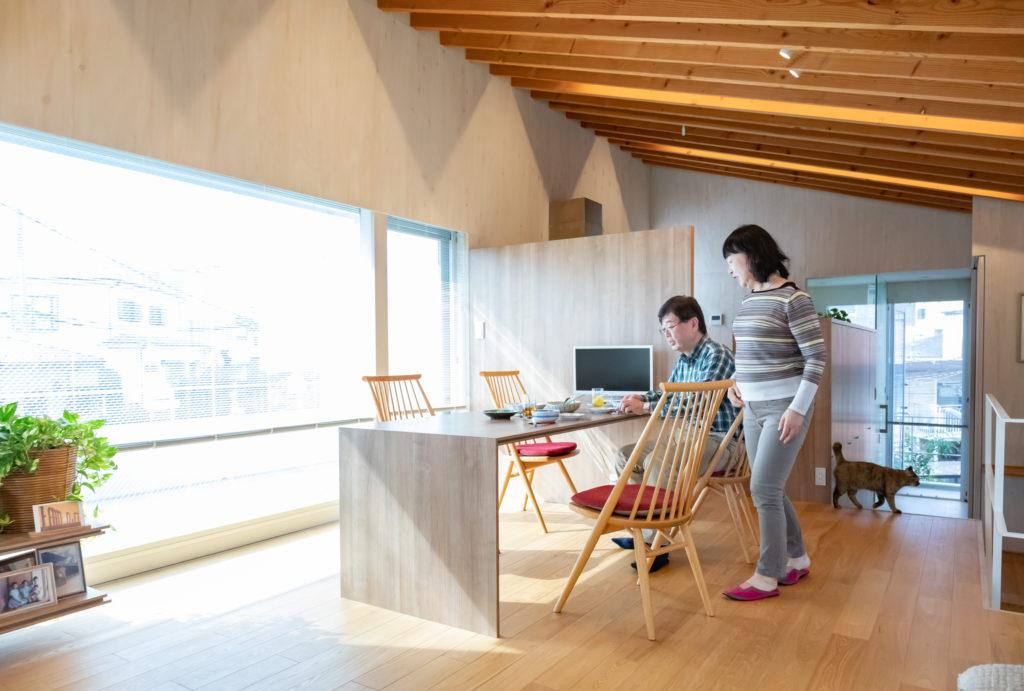 自然と窓に向かって並んで座ることが多いというお2人。華奢でシンプルなテーブルは庄司さんのデザイン。イスは『柏木工』のもの。