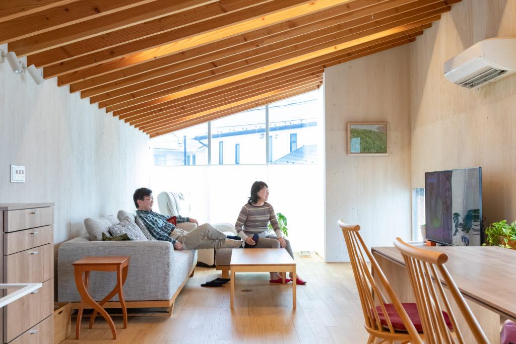 『柏木工』で購入したソファで過ごすひとときは、お2人のお気に入りの時間。奥の開口が道路側。夜は、天井の梁が幻想的に光り、外から見ても美しい。