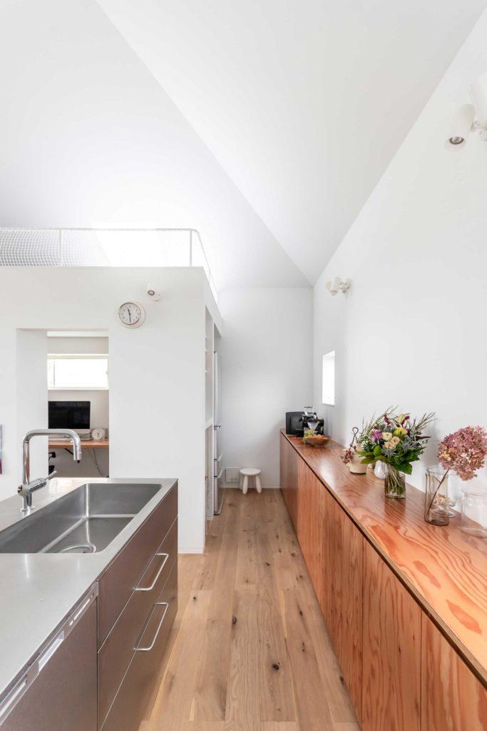 すっきりとした印象のキッチン。冷蔵庫は奥の左側に置かれている。収納家具の素材には合板を使用した。