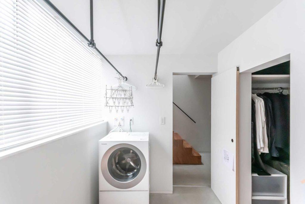 室内干しを前提につくられたスペース。洗濯したものをハンガーにかけて干し、乾いたらそのまま右のクローゼットに収納する。動線に無駄がないうえにたたむ手間も省ける。「空間がつながっている感じにしたかった」ため、戸はすべて引き戸にしている。