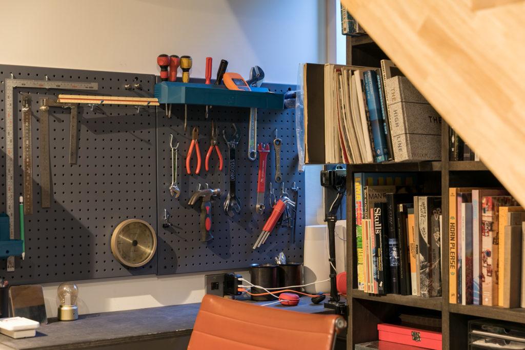 仕事机の向こうのDIYスペース。有孔ボードにツールを吊るす。