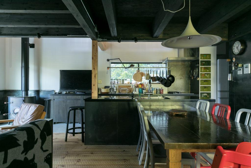 現しにした天井を黒く塗装。キッチンは大勢でのパーティーにも対応できるよう2列に。2階キッチンの開口は、道行く人の目線と同じ高さになっている。