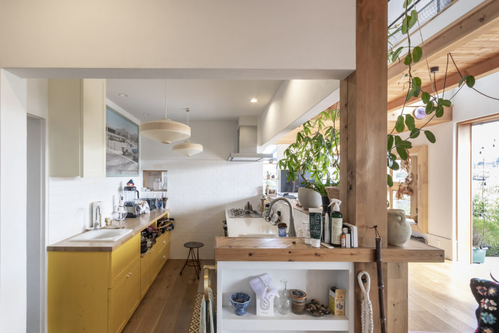 半オープンの明るいキッチン。左奥には勝手口のあるパントリーも。