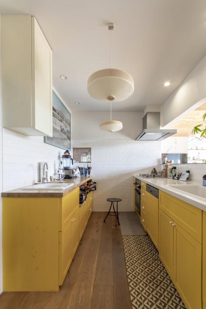 """キッチンには、千明さんの希望で野菜洗い用の浄水のシンクも設置。当初、白×紺だったのを、80年代の映画を見て""""かわいい""""と思い、黄色にチェンジ。"""