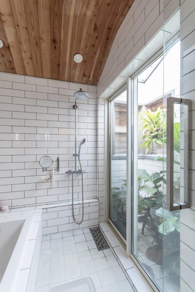 ガラス張りのバスルームは中庭も設けて開放的に。タイルの目地は薄いグリーンで柔らかな雰囲気。