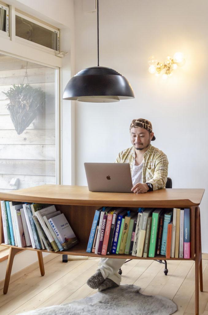 増山大輔さん。アアルトなどの建築洋書も研究。机はヤフオクで見つけた北欧のもの。