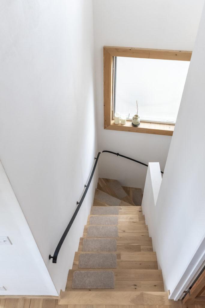 階段は上部にくるほど幅を出すことで、広がりを持たせた。手すりはアイアンでオーダー。