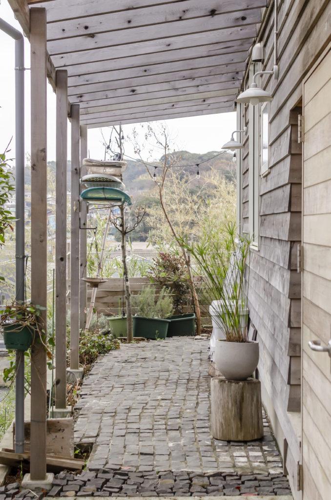 玄関からテラスにつながる小径には、DIYでピンコロ石を。不揃いな雰囲気を楽しんでいる。