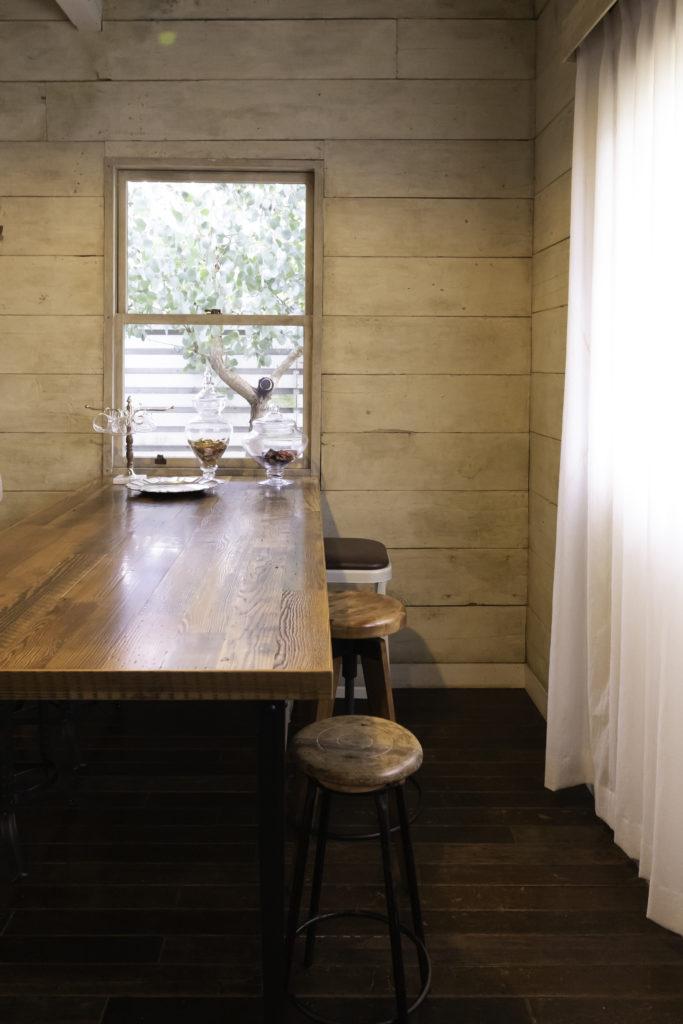 アメリカの古材で作ったダイニングテーブル。スツールで座ってちょうどいい高さにしている。