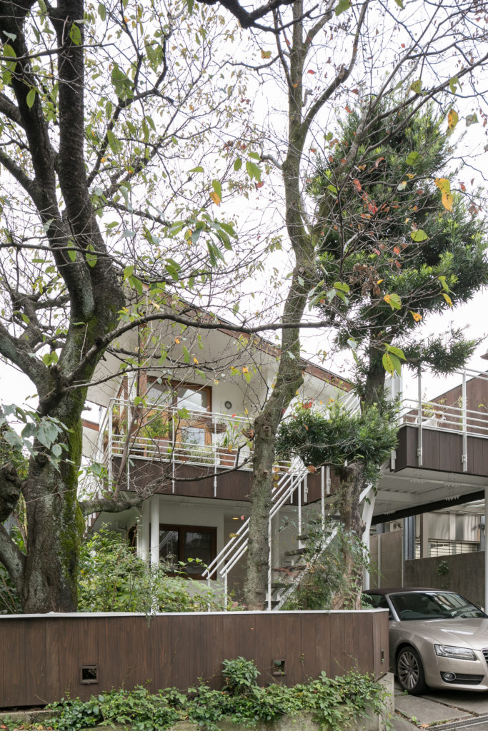 外観の3本のシンボルツリーは20年前よりだいぶ大きくなった。2階のテラスには外からも上がれるようになっていて便利。駐車場の屋根としての役割も併せ持つ。