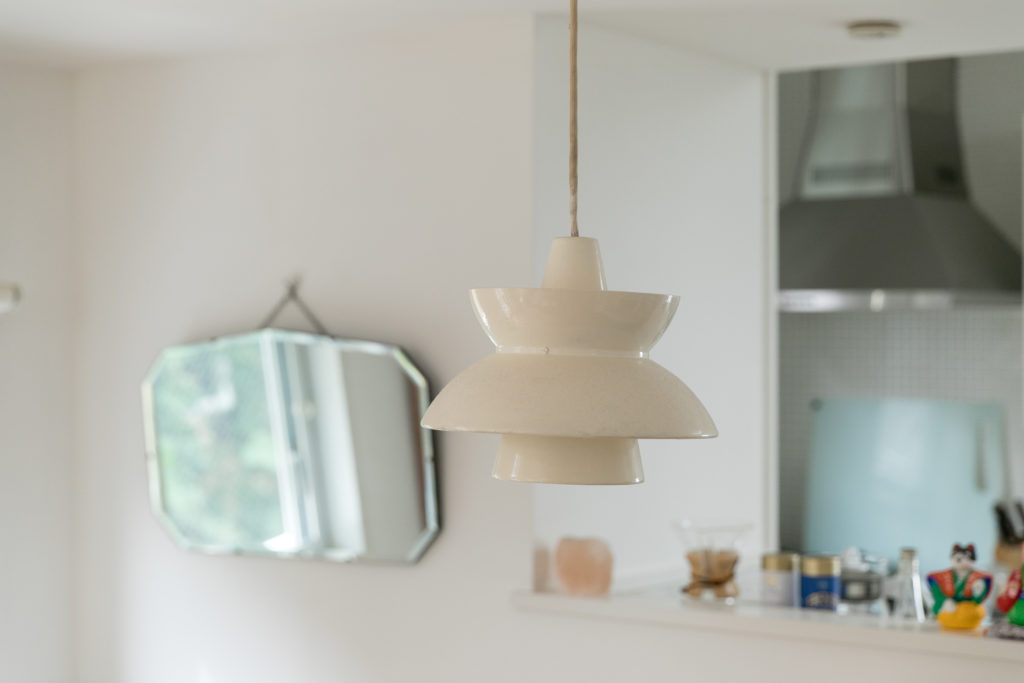 ルイス・ポールセンの照明はヴィンテージ。20年前からずっとリビングを照らし続けている。奥の鏡は目黒通りのアンティークショップで見つけたもの。