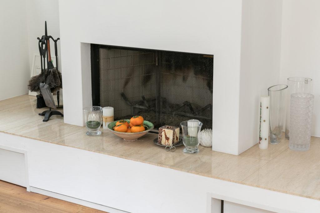 白を基調としたモダンなデザインの暖炉。炉台は耐火性に優れたトラバーチンという石材。冬には火を入れて、揺れる炎や薪のはぜる音でリラックスする。