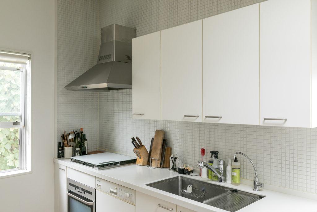 白を基調としたキッチンは、緑が見える窓もあって明るい。ミーレの食洗機、AEGのオーブンなど、しのぶさんが厳選した機器がおさまる。壁面はモザイクタイルにしてあり、素材のグラデーションが楽しい。