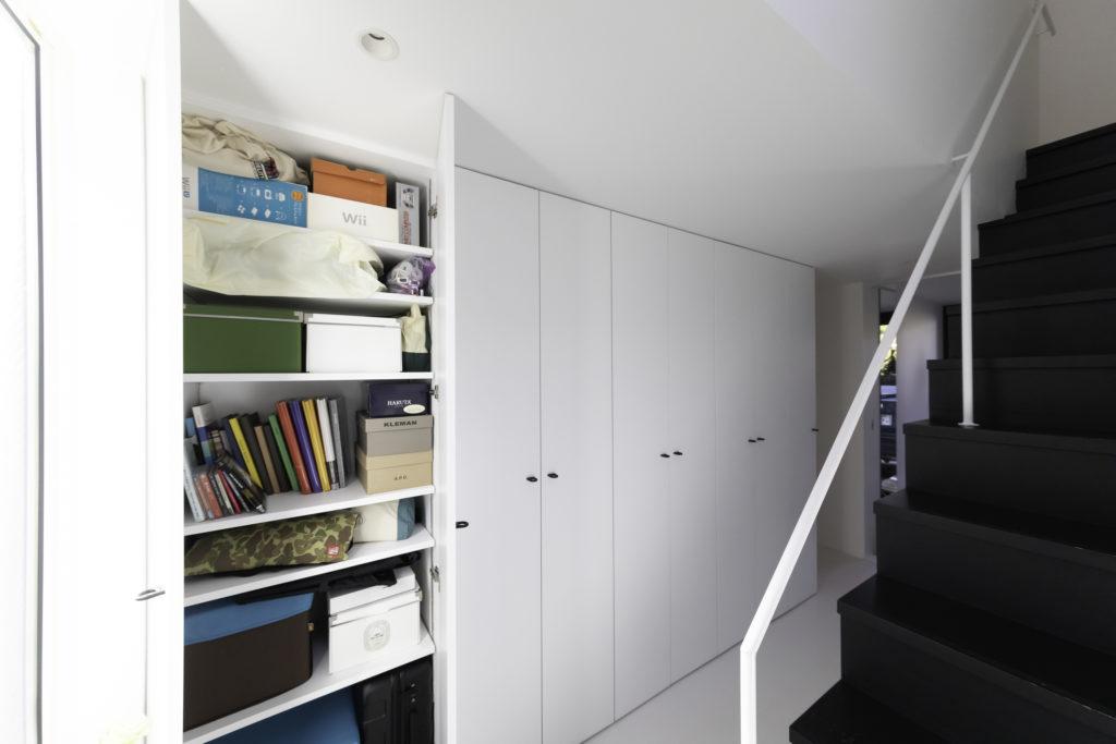 1階廊下に設えた天井までの壁面収納。4人それぞれ専用の収納スペースを持っている。