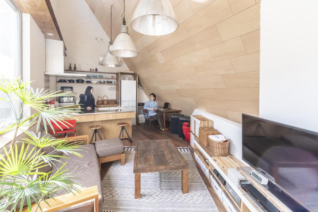キッチン部分の壁は京子さんの希望でブリックタイルを張った。右の木の壁は遊さんが明るい色を選びシナ合板にした。存在感のあるライトはブティックで使われていたのを譲り受けたものという。