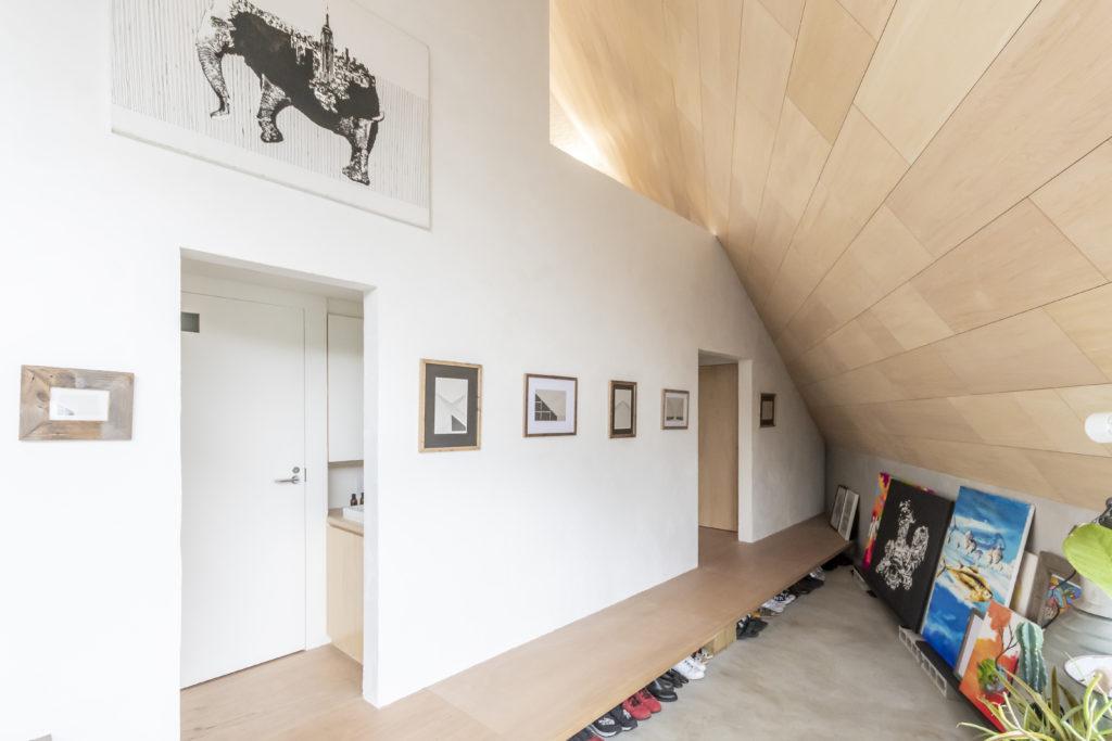 玄関から土間部分に入るとギャラリースペース。真ん中に架けられている作品はこの家のオープンハウスをした際に描かれたこの家をモチーフにしたドローイング。