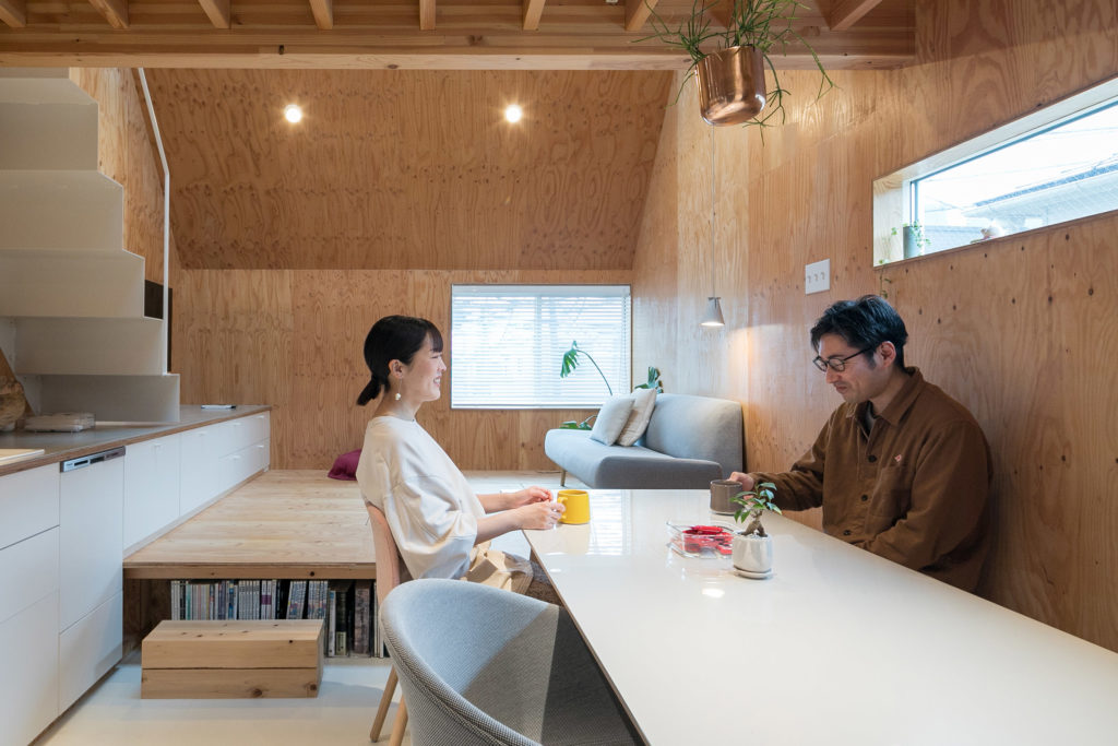 """将毅さんは病院の設計を担当する建築士。休日は自転車に乗り、ふたりで都内のあちこちを回るのが楽しみだそう。""""色と木口の出ているところが空間にぴったりだった""""ダイニングテーブルと、椅子はHAYのもの。小上がり下には本棚も設けられている。"""