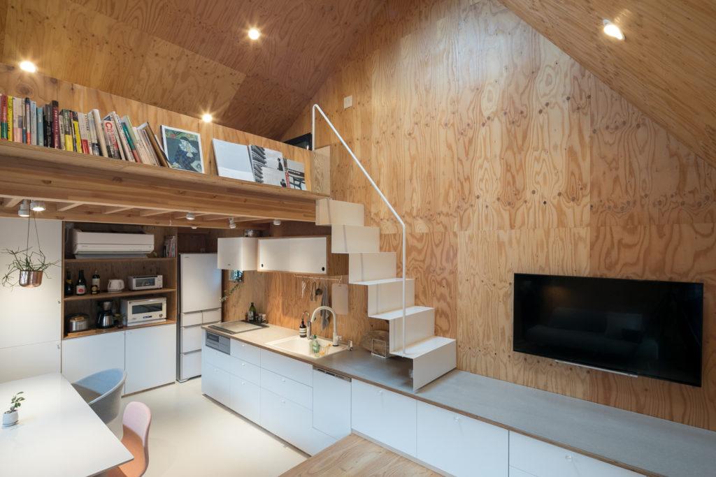 キッチンから小上がり側のテレビ台まで、フレキシブルボードにウレタン塗装をした天板がひとつながりに。オーダーして造った白い鉄製の片持ち階段でロフトにあがる。