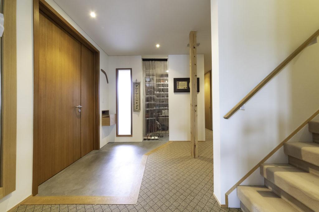 玄関ホール。上履きと下履きを分けられるように、墨モルタルの土間とカーペットで変化をつけた。
