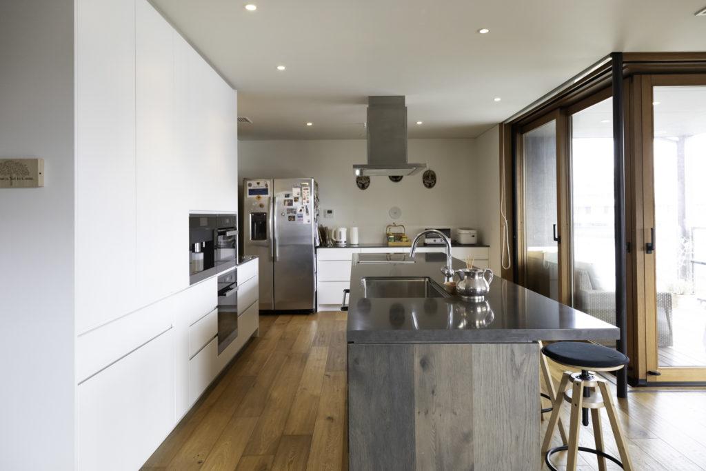 ヴィンテージ風の木目のキッチンを引き立たせる、ピュアホワイトの壁側収納も『キッチンハウス』でオーダー。