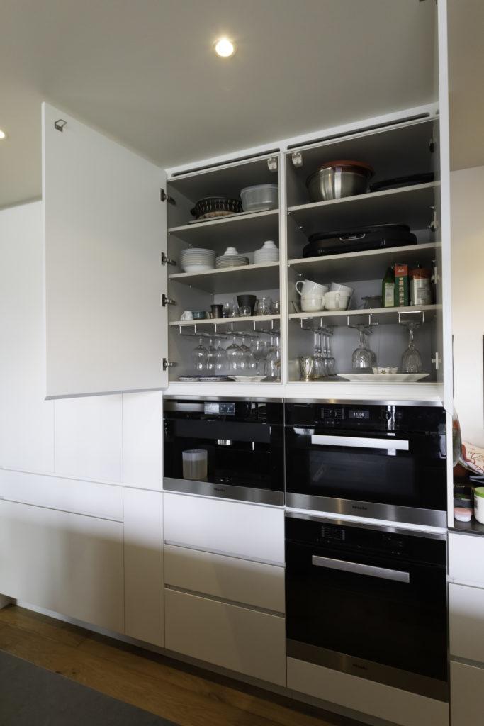 オーブン料理が得意な並子さんのリクエストで、ミーレのオーブンが2つ。ワイングラスは専用のラックをつけて収納。「地震のときも安心です」(並子さん)