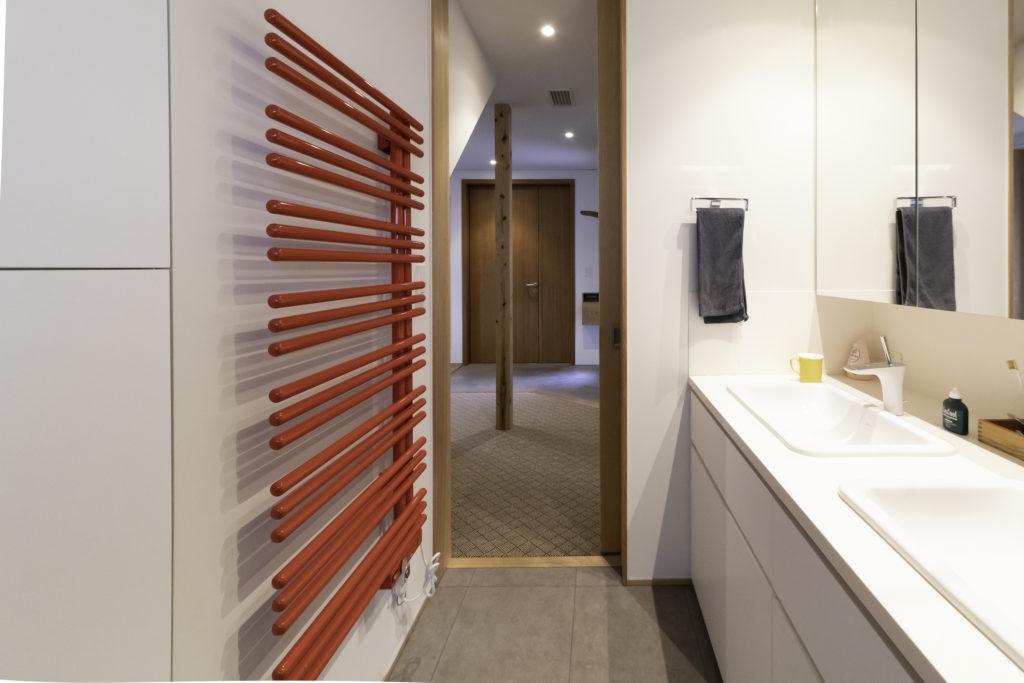 キッチンから玄関へと回遊できるようになっている。左の赤いタオルウォーマーはタオル以外も乾かせて重宝しているとのこと。