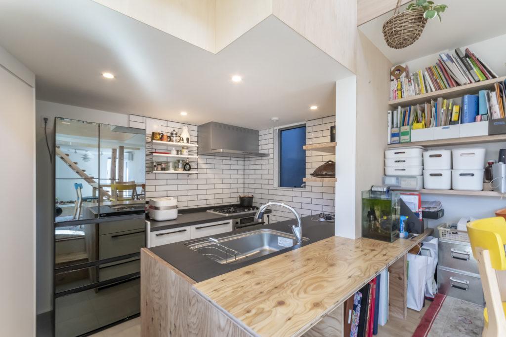 キッチンの天板は料理好きのマミさんの希望で熱いままの鍋も直に置けるセラミックトップに。コンロ周りの壁は清潔に保てるよう黒目地に白のタイルにした。