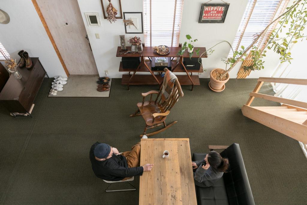 吹き抜けからリビングを見下ろす。ダイニングテーブルは、足場板を使った多一郎さんのハンドメイド。