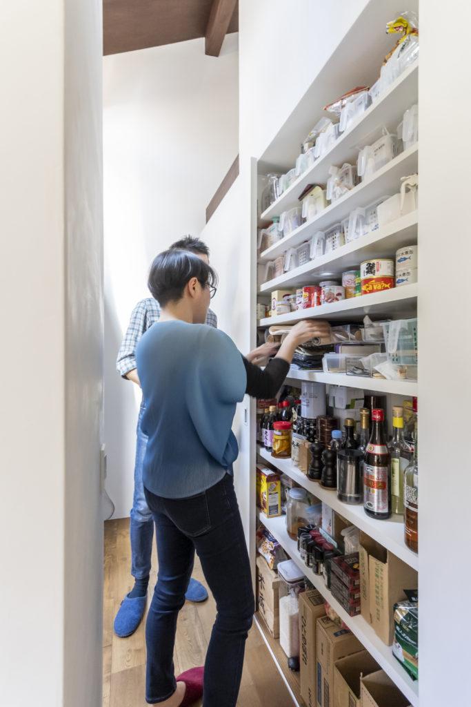 壁のような大きな引き戸を開けると料理に使う調味料や缶詰、お酒などを収納した棚が現れる。