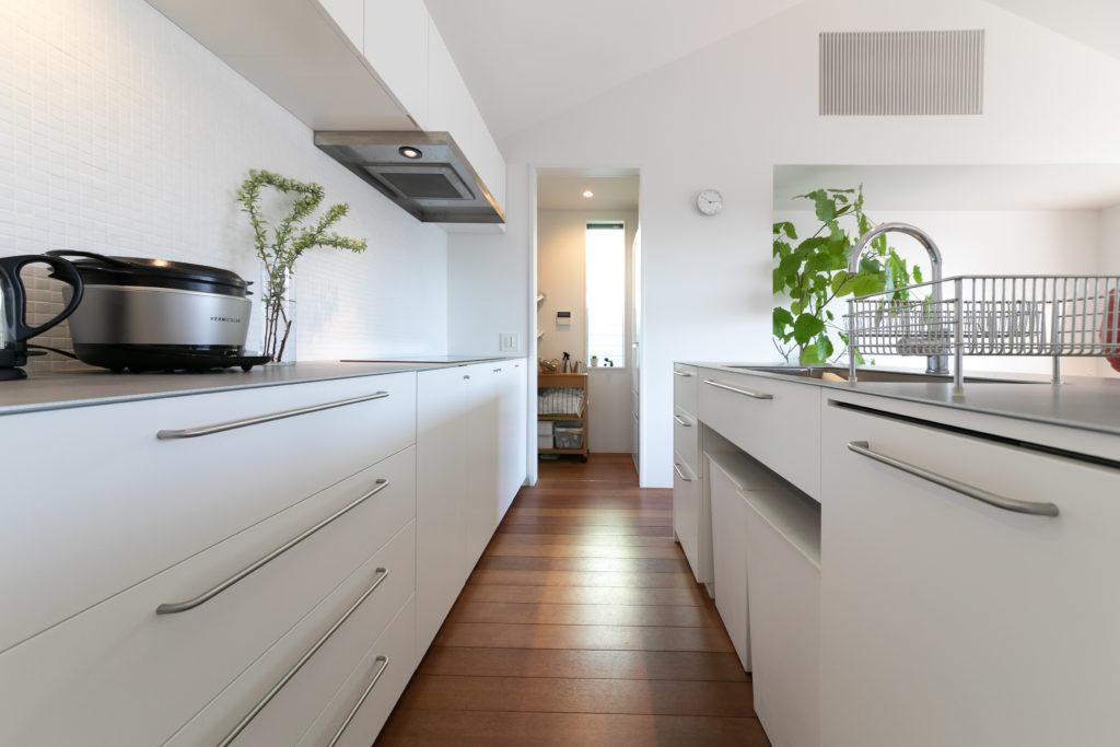 キッチンは建築家の今城さんがデザインした造作。ステンレスの天板と真っ白なキッチン台を濃いめの床材が引き立てる。壁のタイルは野添さん夫妻で貼り付けた。