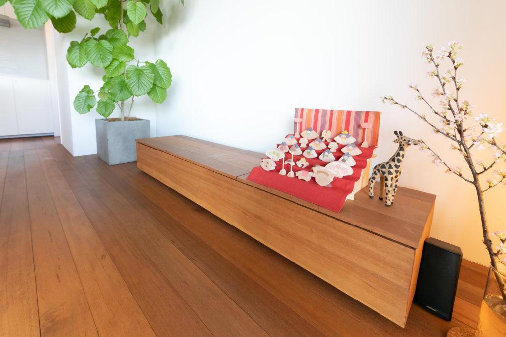床材と同じアピトン材のローボードは聡司さんが造作したもの。ベンチとしても使用可能。撮影時は、組み木のひな人形が可愛らしい空間のアクセントになっていた。