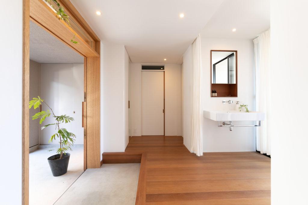 開放的な玄関ホール。引き戸により開口部が広く取れるため、作業するにも便利。洗面台脇のカーテンで仕切ることも可能。