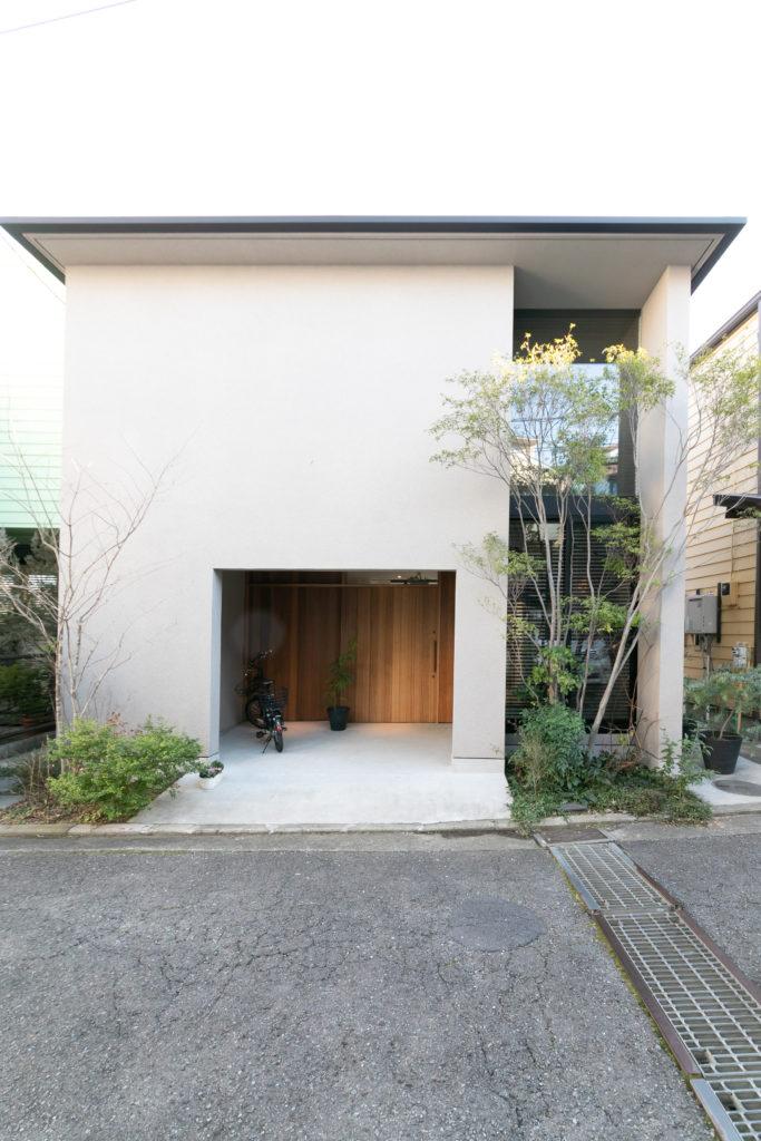 「手入れの楽なものを植えている」という玄関前の植栽。程よく伸びたハイノキ(右側)が、目隠しの役割も。