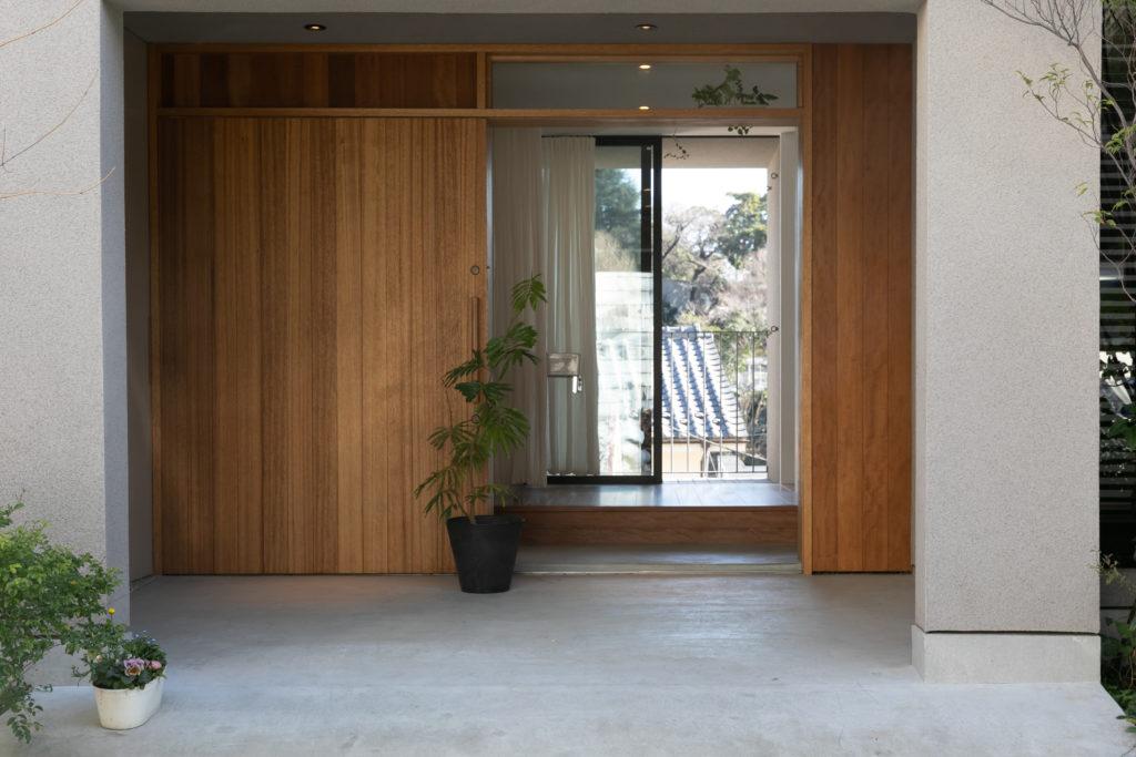温かみのある木製の引が戸が印象的なエントランス。引き戸を開け放つと、玄関前のアプローチから、玄関奥の物干しテラスまで視線が抜ける。