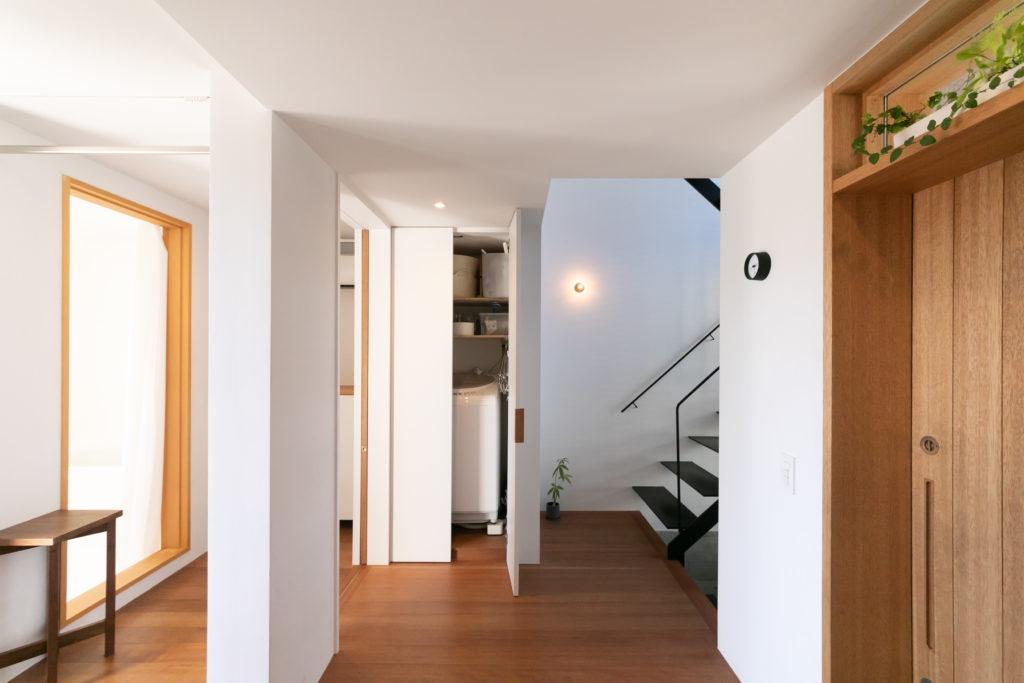 1階には、洗濯の動線を考えて配置したサニタリールームや物干しテラスがある。左側に設けた壁が、玄関からの程よい目隠しになっている。