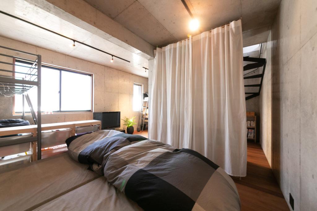 地階とは思えないほど、大きな窓から日差しが入る。カーテンで目隠しした大型収納は聡司さんが作製したもの。