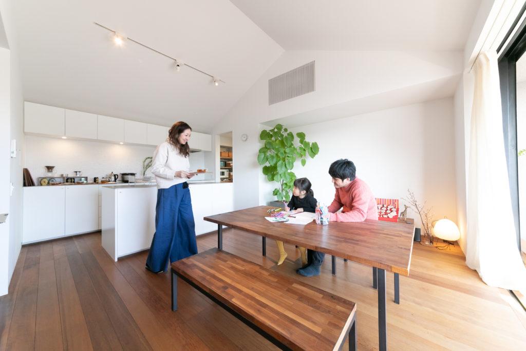ダイニングセットは友人の家具職人にオーダー。「ウォールナットの細かい材を組み合わせたモザイクっぽい感じが気に入っています」(真由美さん)。最後まで悩まれたという照明は、景色やプロジェクターで映し出す映像を邪魔しないようにスポットライトを採用。手元までしっかり明るく照らすプロ仕様のもの。)