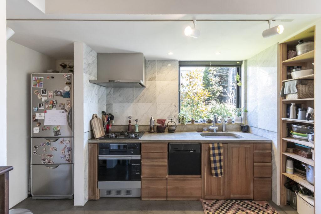 大理石、モルタル、クルミの木の異素材がミックスされたキッチン。右手の食器棚もDIYで。