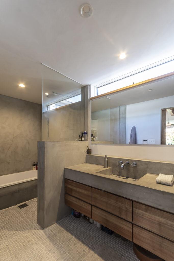 1階のバスルームは、モルタルを使ったシンプルで清潔感のある空間。洗面台も造作。