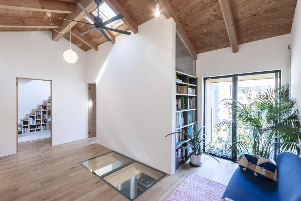 廊下の概念を覆す共用部。DIYで設けた本棚は、奥のゲストルームの仕切り代わりにもなっている。