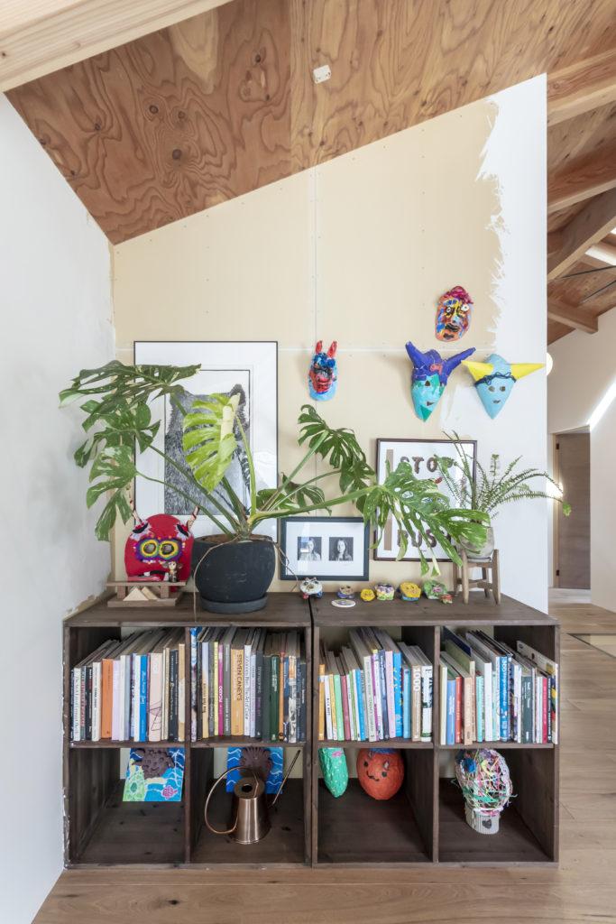 階段を登ると現れる一角。集成材に色を塗りDIYで作った棚を本棚に。壁にはお子さんの作品を飾る。